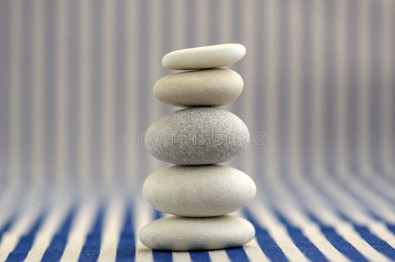 Armonía y balanza, mojón de la roca del guijarro, piedras simples del equilibrio en el fondo rayado blanco y azul, escultura del  fotos de archivo libres de regalías