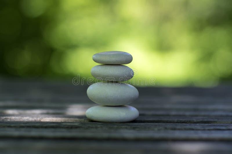Armonia ed equilibrio, cairn, ciottoli semplici di equilibrio sulla tavola di legno, fondo verde naturale, scultura di zen della  fotografia stock libera da diritti