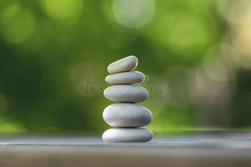 Armonia ed equilibrio, cairn, ciottoli semplici di equilibrio sulla tavola di legno, fondo verde naturale, scultura di zen della  immagine stock libera da diritti