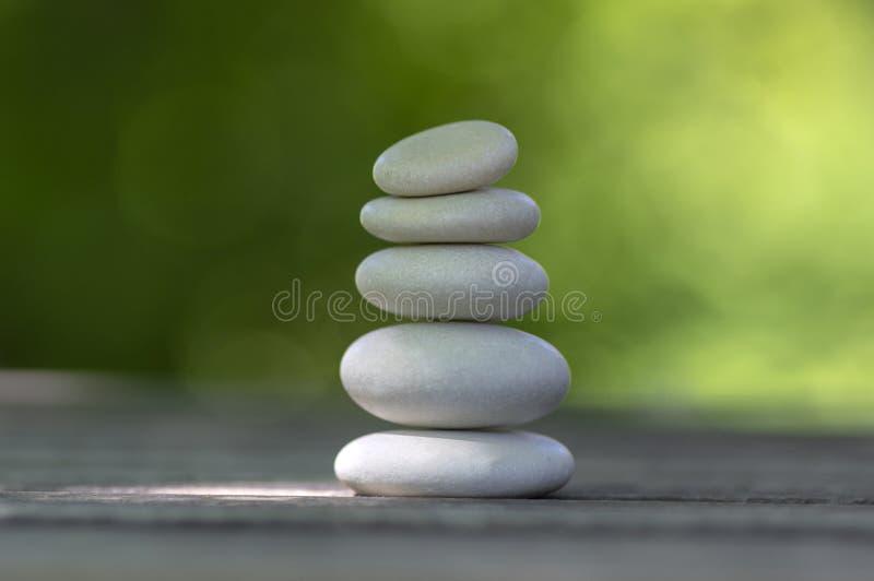 Armonia ed equilibrio, cairn, ciottoli semplici di equilibrio sulla tavola di legno, fondo verde naturale, scultura di zen della  fotografie stock