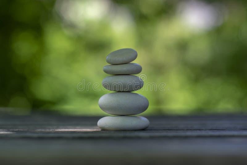 Armonia ed equilibrio, cairn, ciottoli semplici di equilibrio sulla tavola di legno, fondo verde naturale, scultura di zen della  fotografia stock