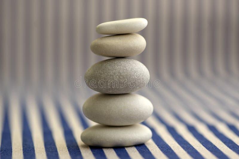 Armonia ed equilibrio, cairn della roccia del ciottolo, pietre semplici di equilibrio su fondo a strisce bianco e blu, scultura d immagine stock libera da diritti