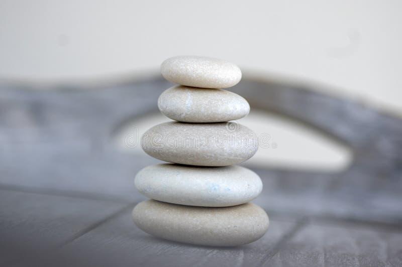 Armonia ed equilibrio, cairn, pietre semplici di equilibrio su fondo bianco, scultura di zen della roccia, cinque ciottoli bianch immagini stock libere da diritti