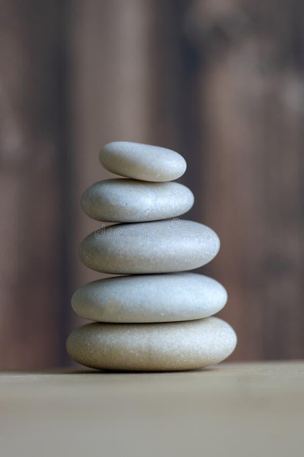 Armonia ed equilibrio, cairn, pietre semplici di equilibrio su fondo bianco, scultura di zen della roccia, cinque ciottoli bianch fotografia stock libera da diritti