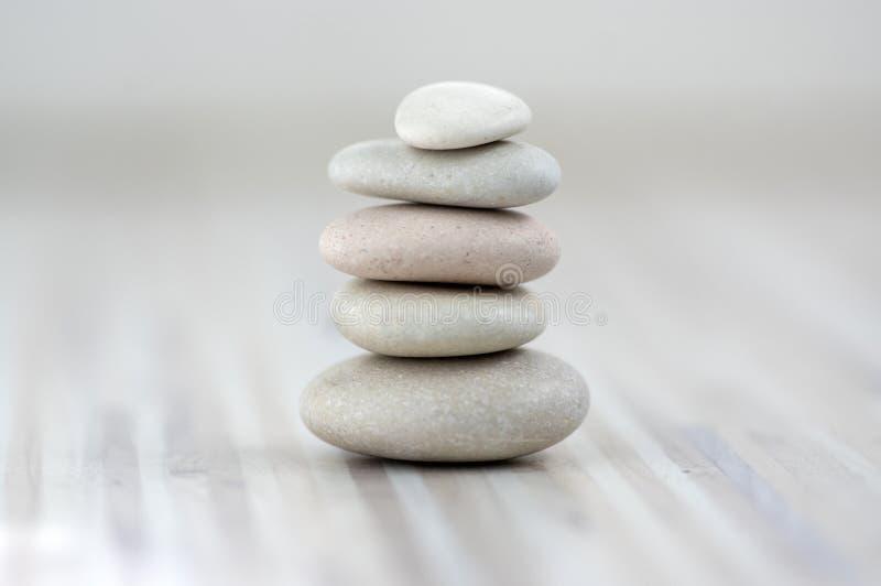Armonia ed equilibrio, cairn, pietre semplici di equilibrio su fondo grigio bianco leggero di legno, scultura di zen della roccia immagini stock
