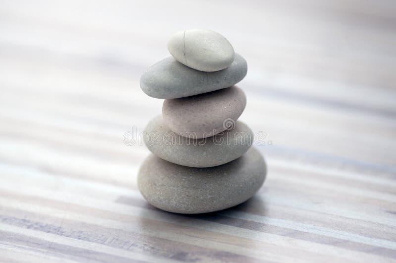 Armonia ed equilibrio, cairn, pietre semplici di equilibrio su fondo grigio bianco leggero di legno, scultura di zen della roccia fotografia stock