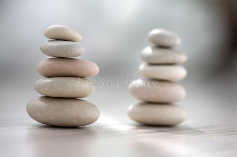Armonia ed equilibrio, cairn, pietre semplici di equilibrio su fondo grigio bianco leggero di legno, scultura di zen della roccia immagine stock