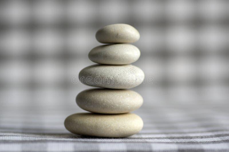Armonia ed equilibrio, cairn, pietre semplici di equilibrio su fondo a quadretti grigio bianco, scultura di zen della roccia, cin fotografia stock