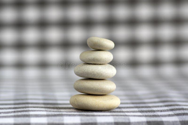 Armonia ed equilibrio, cairn, pietre semplici di equilibrio su fondo a quadretti grigio bianco, scultura di zen della roccia, cin fotografie stock libere da diritti