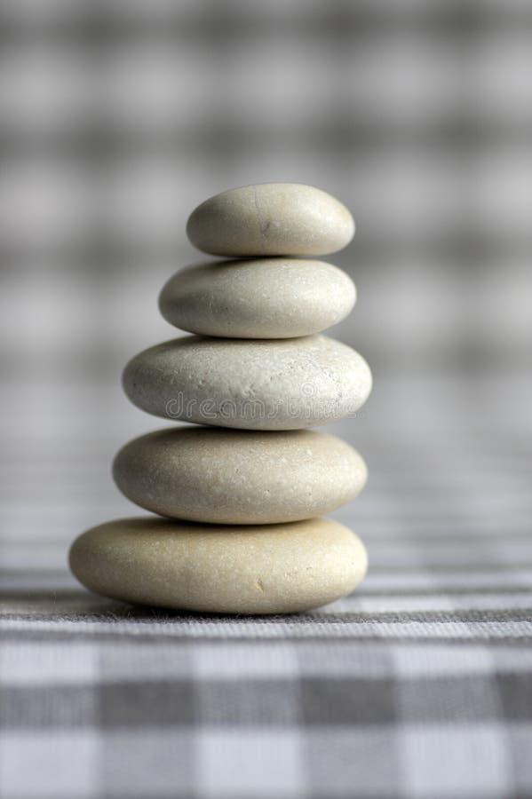Armonia ed equilibrio, cairn, pietre semplici di equilibrio su fondo a quadretti grigio bianco, scultura di zen della roccia, cin immagini stock