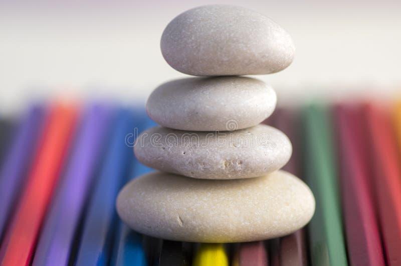 Armonia ed equilibrio, cairn, pietre semplici di equilibrio su fondo variopinto, scultura di zen della roccia, ciottoli bianchi,  fotografia stock