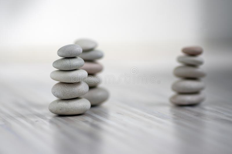 Armonia ed equilibrio, tre cairn, ciottoli semplici di equilibrio su fondo grigio bianco leggero di legno, scultura di zen della  fotografia stock