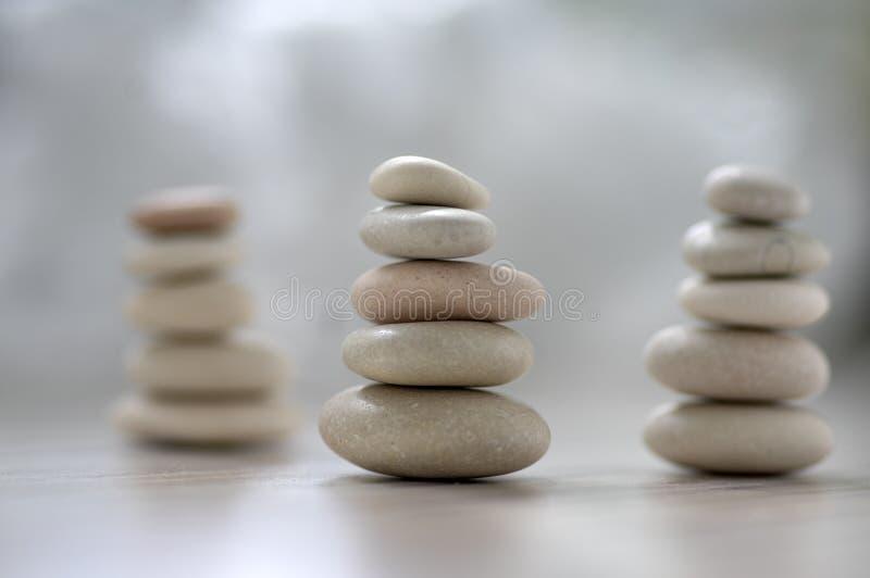 Armonia ed equilibrio, tre cairn, ciottoli semplici di equilibrio su fondo grigio bianco leggero di legno, scultura di zen della  fotografie stock