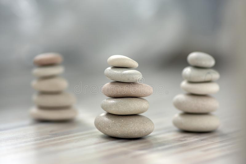 Armonia ed equilibrio, tre cairn, ciottoli semplici di equilibrio su fondo grigio bianco leggero di legno, scultura di zen della  immagine stock libera da diritti