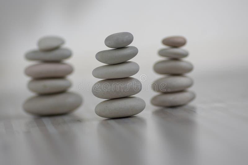 Armonia ed equilibrio, tre cairn, ciottoli semplici di equilibrio su fondo grigio bianco leggero di legno, scultura di zen della  fotografie stock libere da diritti