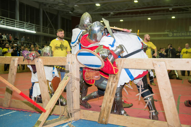 Armored fighters. MOSCOW - DECEMBER 03, 2016: Armored fighters , dressed as knights, fighting at the XI World championship in Medieval combat CUP `DYNAMO`. in royalty free stock photo