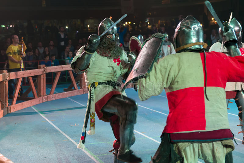 Armored fighters. MOSCOW - DECEMBER 03, 2016: Armored fighters , dressed as knights, fighting at the XI World championship in Medieval combat CUP `DYNAMO`. in stock photography