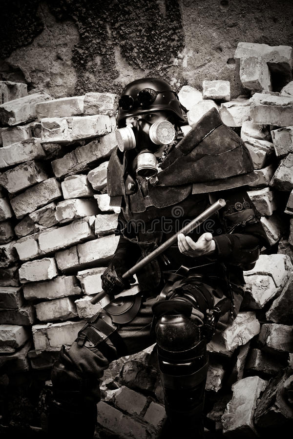 Armored postnuclear warrior with a metal club royalty free stock photo