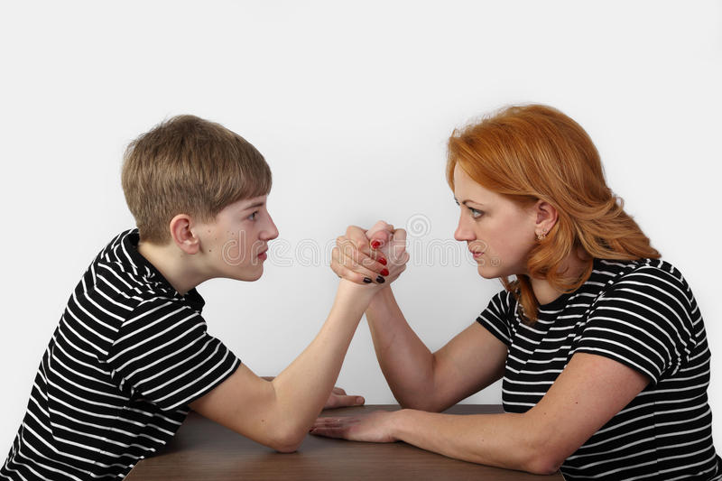 Armrestling on gray. Redhead women and teenage boy in similar t-shirts fight on hands on gray background in square - mother and son armrestling - solution of royalty free stock images