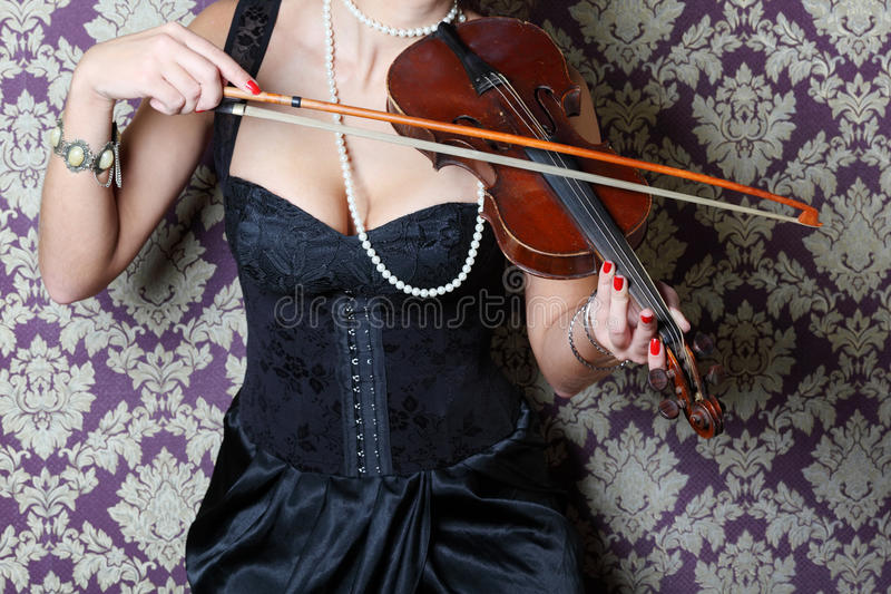 Arms and chest of woman in dress playing violin