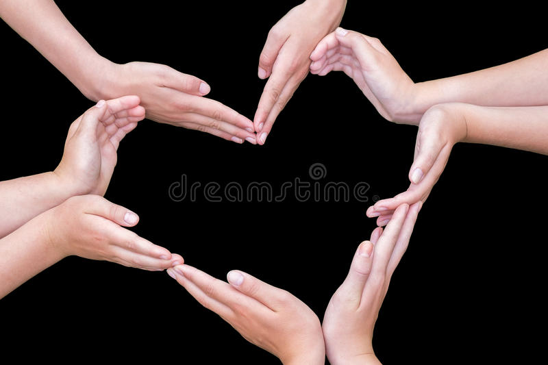 Arms and hands of girls making heart shape. Many arms and hands of teenagers making heart shape isolated on black background royalty free stock photography