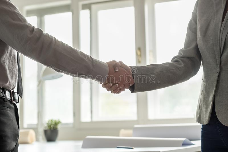 Arms of two businesspeople in suits shaking hands stock photo