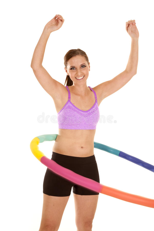 Arms up hoop. A woman in her puple sports bra and shorts working out with a weighted hoola hoop royalty free stock images