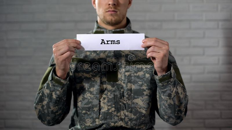 Arms word written on sign in hands of male soldier, weapon arsenal, industry royalty free stock photos