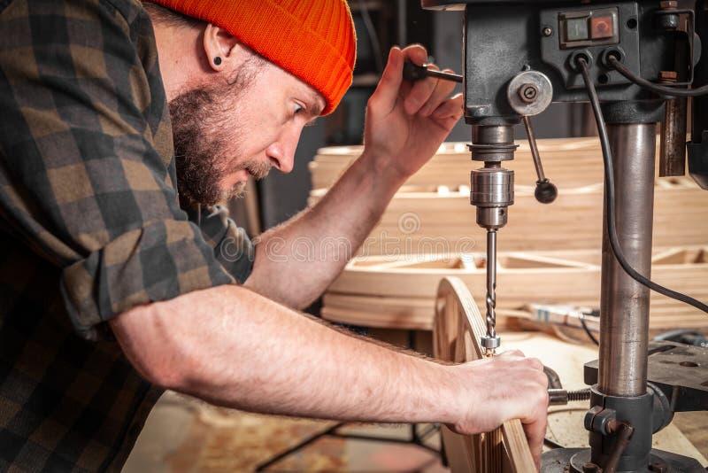 Home repair concepts. Arms of worker  carpenter using electric drilling machine,  closeup. Manual job DIY inspiration improvement job fix shop helmet joinery stock images
