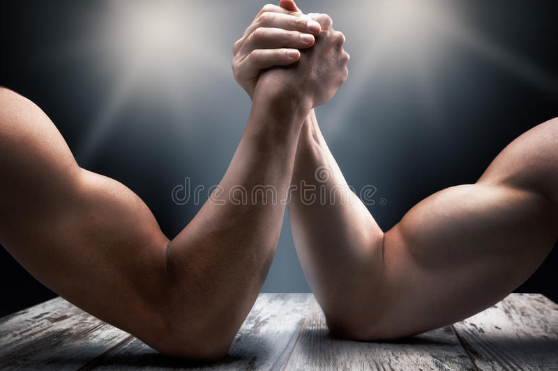 Arms wrestling, competition, strength comparison. Arms wrestling, competition, hands on wooden surface with black background stock photo
