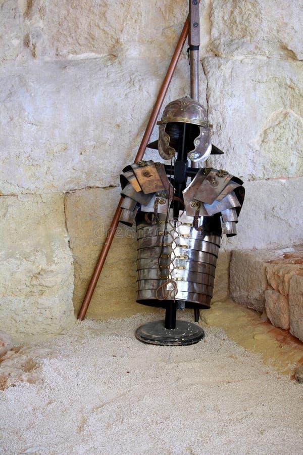 Armure romaine de casque et de corps, montrée contre un mur en pierre photos stock