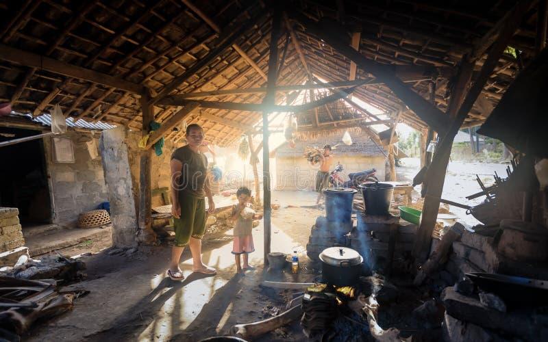 Armutdorfmutter kocht Mahlzeit für ihr Kind unter grundlegendem Schutz stockfoto