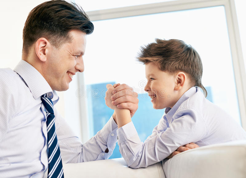 Armwrestling. Young men and his son armwrestling stock image