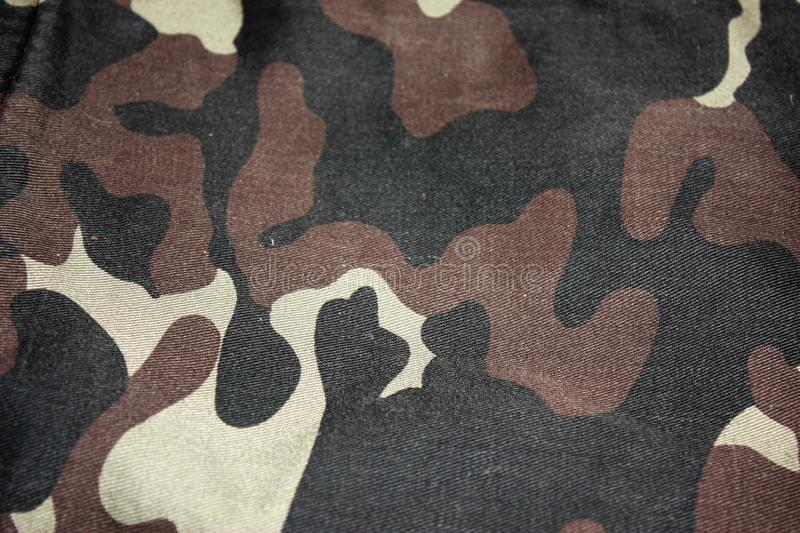 Texture of fabric with a camouflage painted in colors of the marsh. Army background image. Textile pattern of military royalty free stock photos