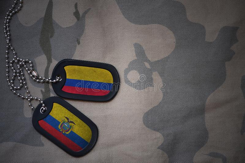 army blank, dog tag with flag of colombia and ecuador on the khaki texture background. royalty free stock photo