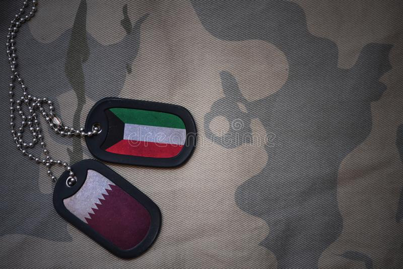Army blank, dog tag with flag of kuwait and qatar on the khaki texture background. Military concept stock photo