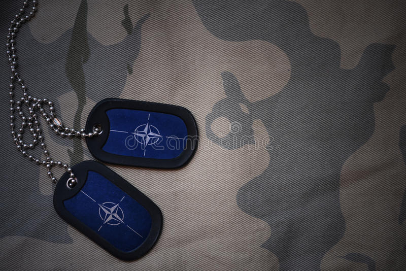 Army blank, dog tag with flag of nato on the khaki texture background. royalty free stock photos