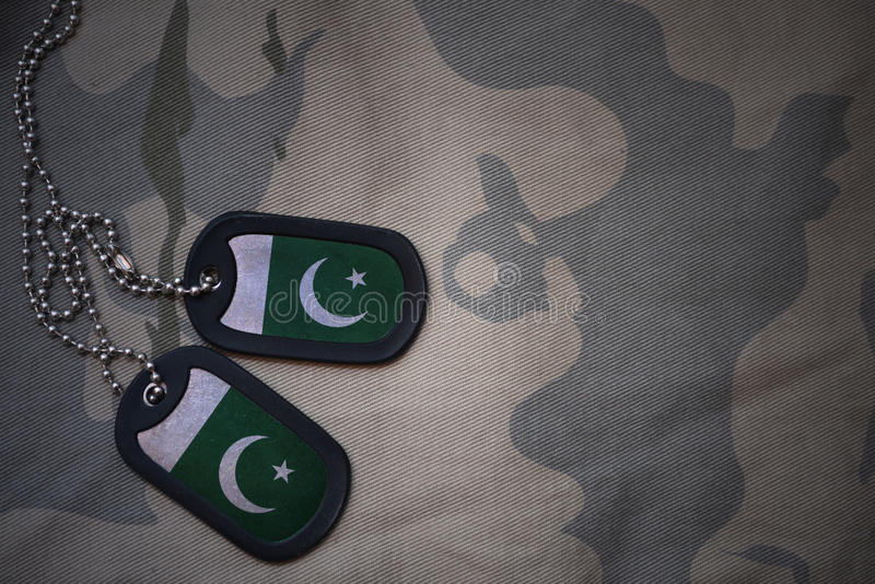 Army blank, dog tag with flag of pakistan on the khaki texture background. royalty free stock images