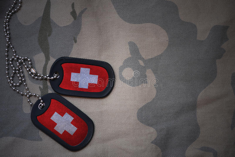 Army blank, dog tag with flag of switzerland on the khaki texture background. stock photo
