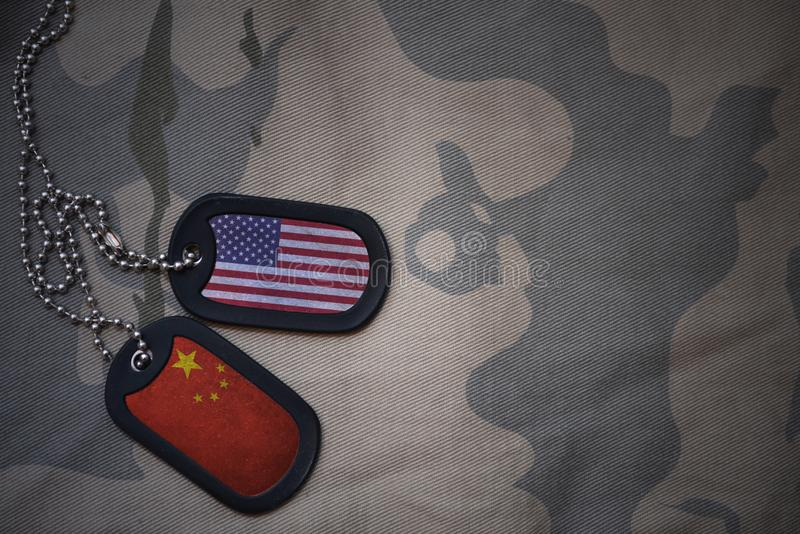 army blank, dog tag with flag of united states of america and china on the khaki texture background. stock photo