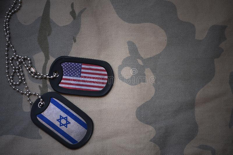 army blank, dog tag with flag of united states of america and israel on the khaki texture background. stock image