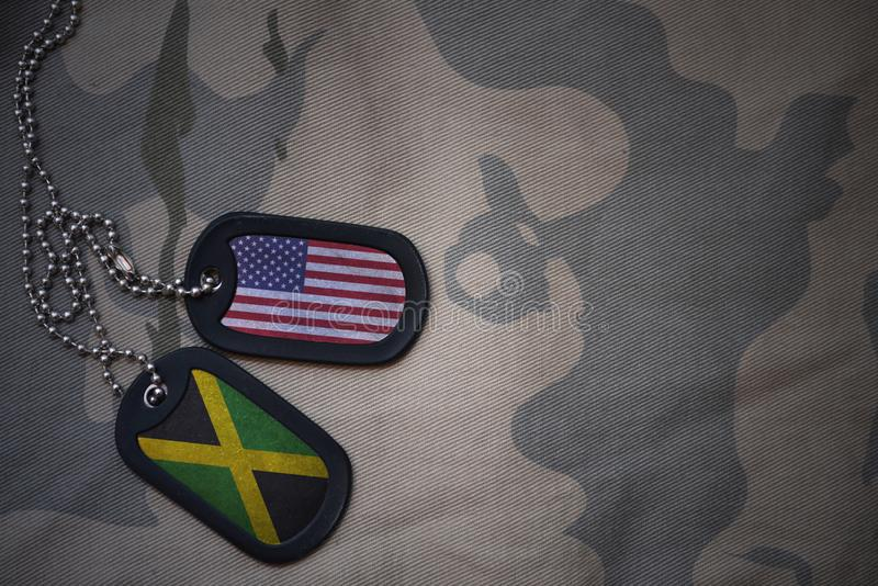 Army blank, dog tag with flag of united states of america and jamaica on the khaki texture background. Military concept stock image