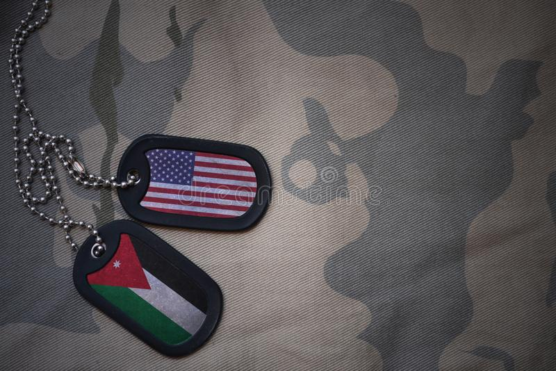 Army blank, dog tag with flag of united states of america and jordan on the khaki texture background. Military concept stock photos