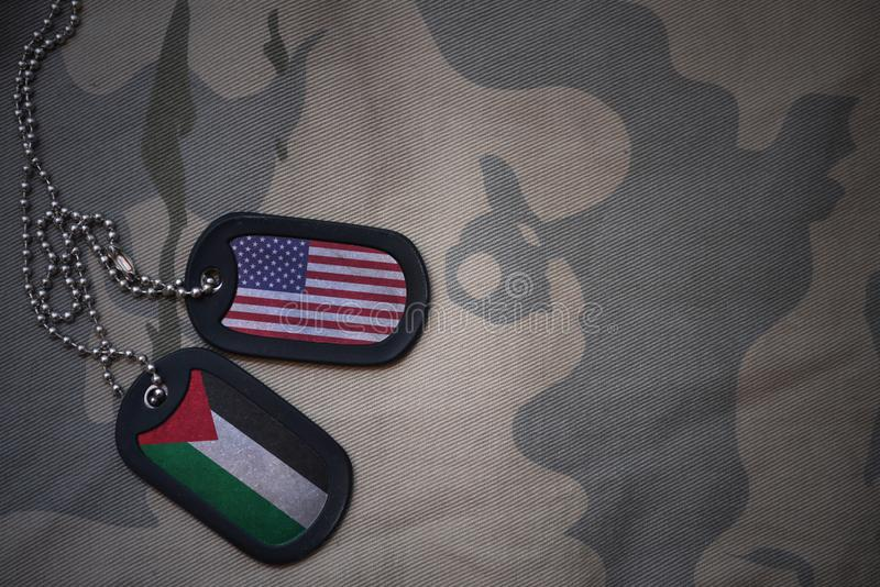 Army blank, dog tag with flag of united states of america and palestine on the khaki texture background. Military concept stock photos