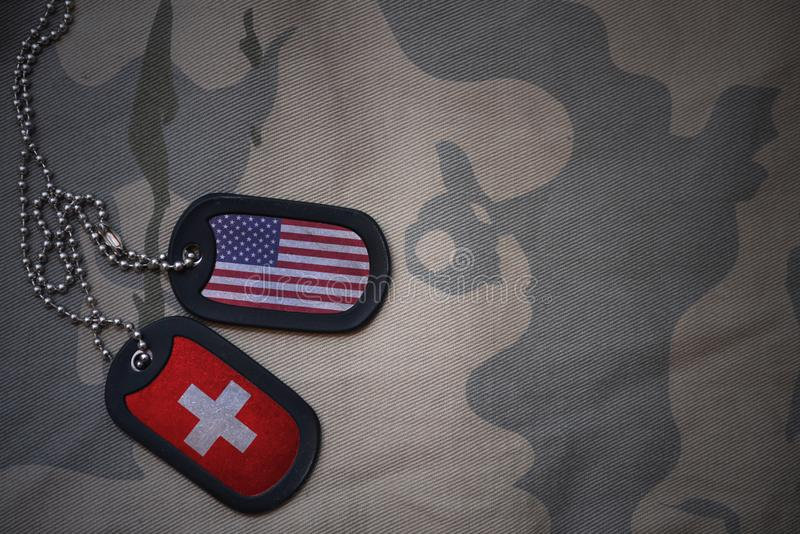 Army blank, dog tag with flag of united states of america and switzerland on the khaki texture background. Military concept royalty free stock images