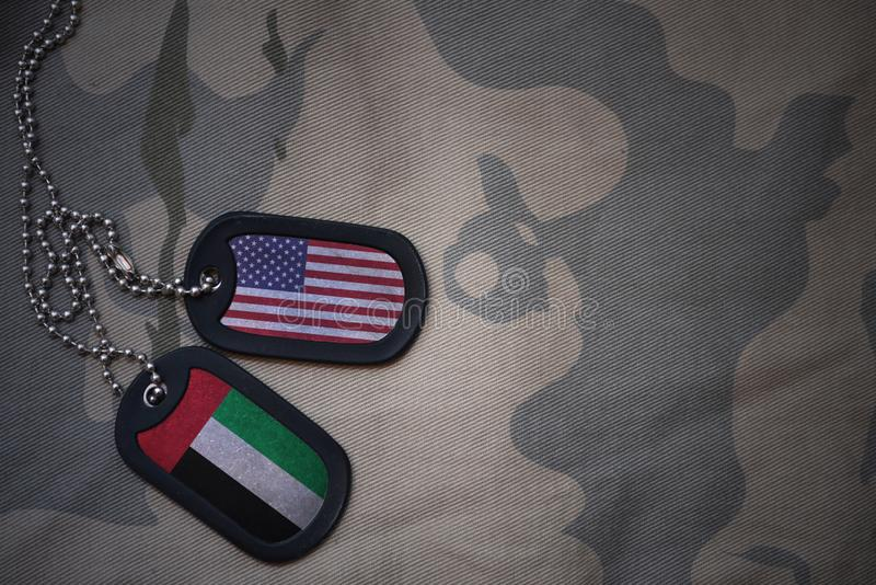 Army blank, dog tag with flag of united states of america and united arab emirates on the khaki texture background. Military concept stock photos