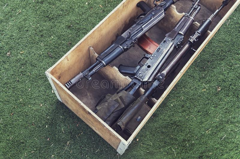 Army box ammunition with AK47 rifle and ammunition. An automatic weapon with a sniper scope in wood box stock image
