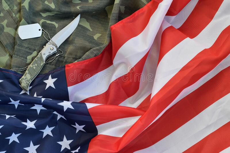 Army dog tag token and knife lies on Old Camouflage uniform and folded United States Flag. Background for Veterans day design stock photos