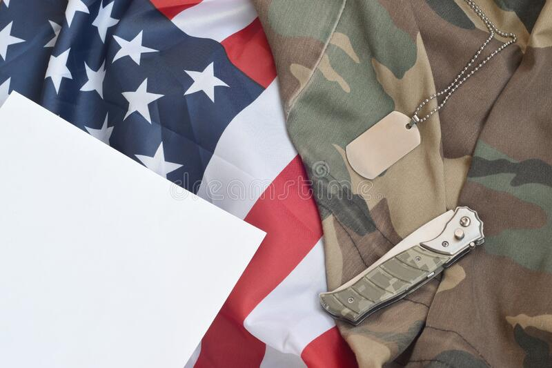 Army dog tag token and knife lies on Old Camouflage uniform and folded United States Flag. Background for Military day design stock photography
