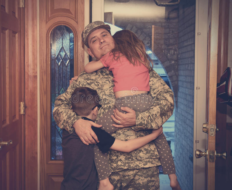 Army Father Coming Home to Family. An army soldier men is coming home in the door and hugging his children for a love, family or reunited concept stock image